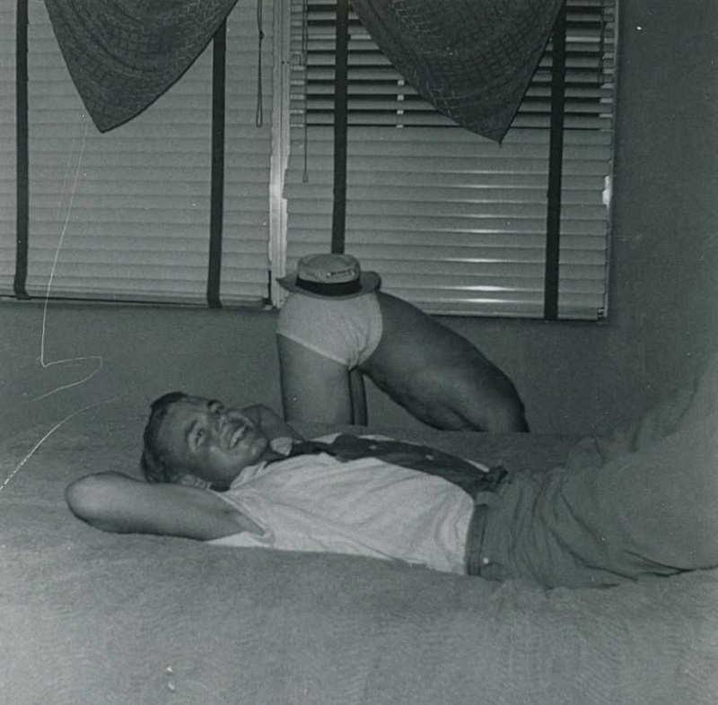 Jack Phillips relaxing on the bed while Dick Albright models his hat.
