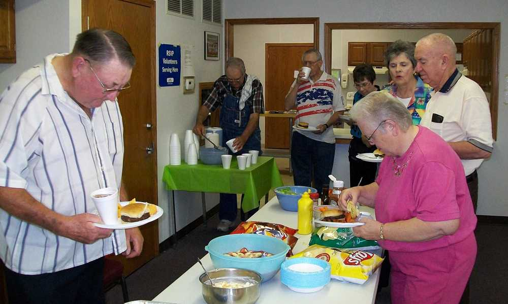 Bill Dunnell balances his plate well while Marion Futhey serves up drinks.